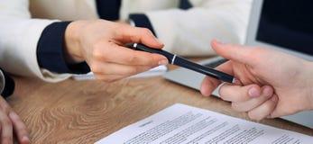 给笔的女商人准备好的商人签合同 成功通信在会议或交涉上 库存照片
