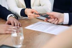 给笔的女商人准备好的商人签合同 成功通信在会议或交涉上 库存图片