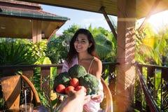 给美丽的妇女板材新鲜蔬菜Pov女孩愉快微笑的男性手坐在热带的夏天大阳台 图库摄影