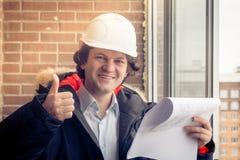 给翘拇指的杂物工 有图纸的工程师在砖背景 与喜悦的微笑的愉快的建造者 软绵绵地集中 库存图片