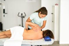 给肩膀按摩的专业女性生理治疗师a 免版税库存图片