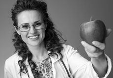 给苹果的微笑的儿科医生妇女  免版税图库摄影