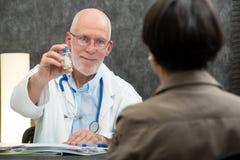 给药片的成熟医生在他的患者 免版税图库摄影