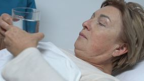 给药片的护士在床,无可救药的疾病,医疗保健上的女性患者 股票视频