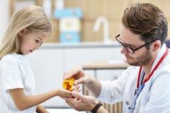 给药片的男性医生小女孩 免版税库存图片