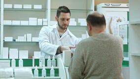 给药物老人顾客和采取付款以美元的年轻药剂师在药房 免版税库存图片
