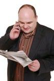 给读取打电话的报纸 免版税库存照片