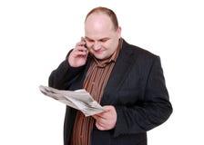 给读取打电话的报纸 免版税库存图片