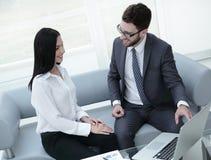 给谈论坐在一台开放膝上型计算机前面的财政文件雇用职员 库存照片