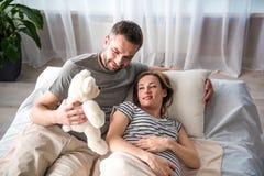 给软的玩具的高兴的未来父亲他的预期妻子 图库摄影