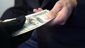 给金钱的商人递在黑手套,罪行概念贿款 免版税库存照片