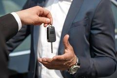 给钥匙的代理年轻人身分在汽车特写镜头附近 库存照片
