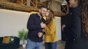 给钥匙的友好的地产商的慢动作新房的美丽的年轻夫妇买家,愉快的配偶亲吻和 股票录像