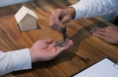 给钥匙的房地产开发商顾客在合同signatu以后 免版税库存图片