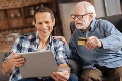 给银行卡的年长人做网上购物的儿子 图库摄影