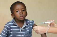 给非洲黑人男孩针射入的白医生作为接种 免版税库存照片