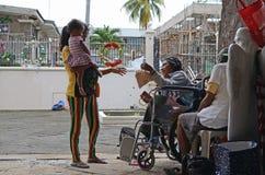 给面包药丸的轮椅叫化子孕妇拥抱的孩子作为礼物在圣诞节时间 库存照片