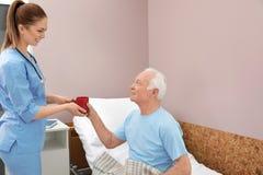 给饮料的护士老人 医疗协助 库存照片