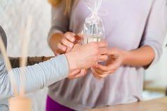 给香水礼物的妇女她的朋友 免版税图库摄影