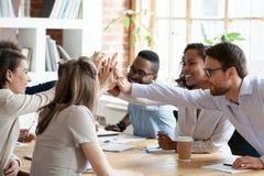 给高五的激动的多种族队在公司会议上 免版税库存照片