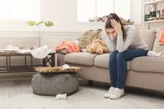 绝望妇女坐沙发在杂乱屋子里 免版税图库摄影