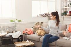 绝望妇女坐沙发在杂乱屋子里 图库摄影