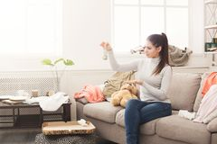 绝望妇女坐沙发在杂乱屋子里 库存图片