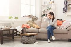 绝望妇女坐沙发在杂乱屋子里 免版税库存照片