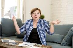 绝望妇女银行业务和会计家庭月度和信用卡费用与做文书工作的计算机膝上型计算机 免版税库存照片