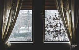 绝热窗口救球能耗下雪秋天视图冬天黑暗的窗帘待在家里下雪外面 库存照片