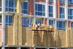 绝缘房子门面的建筑工人 外在墙壁绝缘材料系统或EWIS矿棉节能的 图库摄影