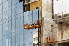 绞刑台电梯的工作者在新的大厦门面安装玻璃窗在伏尔加格勒 免版税库存照片