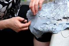 绣一件手工制造礼服的妇女 今天,剪裁可以叫作为一个艺术性的行业 免版税图库摄影