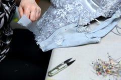绣一件手工制造礼服的妇女 今天,剪裁可以叫作为一个艺术性的行业 图库摄影