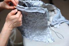 绣一件手工制造礼服的妇女 今天,剪裁可以叫作为一个艺术性的行业 免版税库存照片