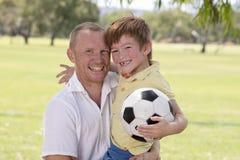 继续他的后面的年轻愉快的父亲激发7或8岁一起踢在城市公园庭院的儿子足球橄榄球摆在s 免版税库存图片