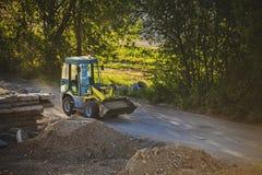 继续前进一条多灰尘的路的小挖掘机汽车 免版税库存图片