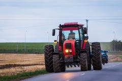 继续前进柏油路的农业拖拉机在工作在领域以后 库存照片