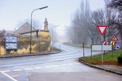 继续前进绕乡下公路的车通过历史镇在一个有雾的冬日 Guntersdorf,下奥地利州 图库摄影