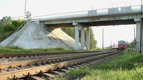 继续前进铁路的电车在汽车桥梁下 在路轨途中的现代火车 影视素材