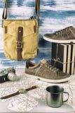 继续旅行:一张大老卡片、行家袋子、运动鞋、三本书、一台减速火箭的照相机、杯子和手表 库存照片