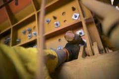 绳索通入戴着安全手套使用电池吵闹声枪和紧固在工地工作的矿工手螺栓 免版税库存图片