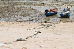绳索附加对在海滩的一个渔船。 库存图片