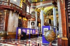 维也纳,奥地利- 2014年5月04日:与梯子的老在奥地利国立图书馆里面的bookshelfs和书 游人参观展览 图库摄影