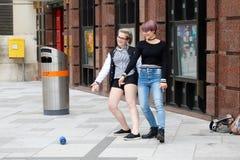 维也纳,奥地利- 2017年9月02日:两个女孩在街道跳舞 从一位便携式的报告人的音乐 免版税库存照片