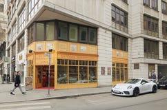 维也纳,奥地利- 2018年4月15日:白色汽车保时捷在一个现代大厦附近停放了 免版税库存图片