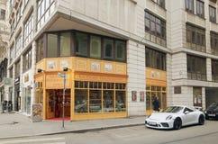 维也纳,奥地利- 2018年4月15日:白色汽车保时捷在一个现代大厦附近停放了 库存照片