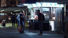 维也纳,奥地利- 2017年8月11日 买快餐的青年人在街道摊在晚上 库存照片