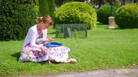 维也纳,奥地利- 2017年8月12日 使用她巧妙的电话的少妇在公园 免版税库存照片