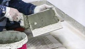 维修服务 放置地板陶瓷砖 人在手套的` s手与小铲,在陶瓷地垫的被涂的水泥灰浆 免版税库存图片